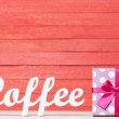 Abstract wooden word Coffee with gift on red wood background. — Stock Photo #48815415