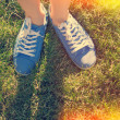 Blue sneakers on saturated green grass. Photo in old color image — Stock Photo #48815773