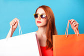Style redhead women holding shopping bags on blue background. — Stockfoto