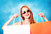 Style redhead women holding shopping bags on blue background. — Foto de Stock