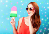 Redhead girl with toy ice cream on blue background. — Stock Photo