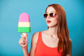 Redhead girl with toy ice cream on blue background. — Foto Stock