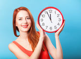 Redhead girl with huge clock on blue background. — Stock Photo