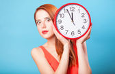 Redhead girl with huge clock on blue background. — Stockfoto