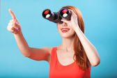 Redhead girl with binocular on blue background. — Stock Photo