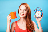 Redhead girl with tea cup and huge clock on blue background. — Stock Photo