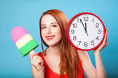 Redhead girl with toy ice cream and huge clock on blue backgroun — Stock Photo