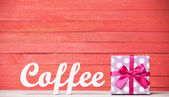 Abstract wooden word Coffee with gift on red wood background. — Stock Photo