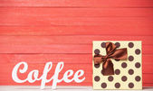 Soyut ahşap kelime hediye ile kahve kırmızı ahşap zemin üzerinde. — Stok fotoğraf