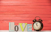 Alarm clock and wooden word Love. — Stock Photo
