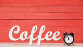 Alarm clock and wooden word Coffee. — Stock Photo