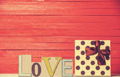 Little gift and word Love on wooden table. — Stockfoto
