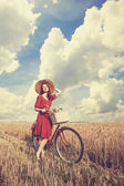 Redhead peasant girl with bicycle on wheat field. — Stock Photo