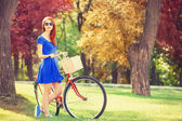 Redhead with bicycle in the park. — Stockfoto