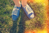 Blue sneakers on saturated green grass. Photo in old color image — Stock Photo