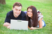 Teen couple with notebook in the park — Stock Photo