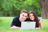 Teen couple with notebook in the park — Stockfoto