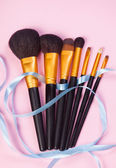 Brushes on pink background. — Stock Photo