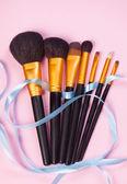 Brushes on pink background. — Stock Photo