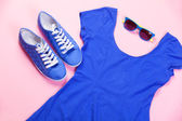 Gumshoes, sunglasses and dress on pink background. — Stock Photo