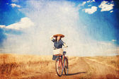 Brunette girl  with bycicle on countryside road. — Stock Photo