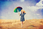 Brunette girl  with umbrella on country side road. — Stock Photo