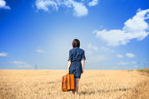 Brunette girl  withsuitcase on wheat field. — Stock Photo