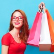 Redhead girl with shopping bags on blue background. — Stock Photo #49514563