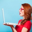 Redhead girl with laptop on blue background. — Stock Photo #49514577
