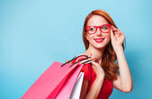 Redhead girl with shopping bags on blue background. — Stok fotoğraf
