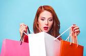 青色の背景色の買い物袋で驚いて赤毛の女の子. — ストック写真