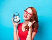 Redhead girl with alarm clock on blue background. — Stock Photo