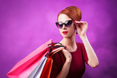 Redhead women with shopping bags on purple background. — Stock Photo