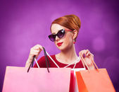 Redhead women with shopping bags on purple background. — Stok fotoğraf