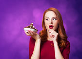 Redhead women with candy on violet background. — Stock Photo
