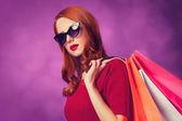 Redhead women with shopping bags on purple background. — Zdjęcie stockowe