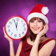 Brunette girl with huge clock and hat on violet background. — Stock Photo #50306405