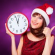 Brunette girl with huge clock and hat on violet background. — Stock Photo #50306465