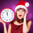 Brunette girl with huge clock and hat on violet background. — Stock Photo #50306469