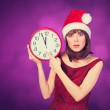 Brunette girl with huge clock and hat on violet background. — Stock Photo #50306475