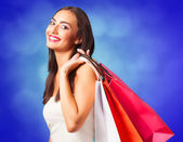 Brunette girl with shopping bags on blue backgorund. — Stock Photo