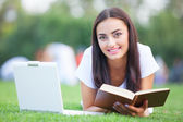 Brunette girl with notebook and book on green grass in the park. — Stock Photo