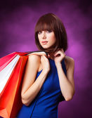 Brunette girl with shopping bags on violet background. — Stock fotografie