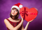 Girl in xmas hat with gift box on violet background. — Foto de Stock
