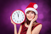 Brunette girl with huge clock and hat on violet background. — Stock Photo
