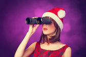Brunette girl with binocular and hat on violet background. — Stock Photo