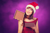 Girl in xmas hat with gift box on violet background. — Stockfoto