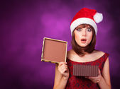 Girl in xmas hat with gift box on violet background. — Stok fotoğraf