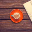 Cup of coffee with heart shape and notebook on wooden table. — Stock Photo
