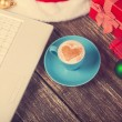 Cup of coffee with heart shape, laptop and christmas gifts. — Stock Photo #50635443